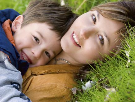 אמא וילד מחובקים על דשא