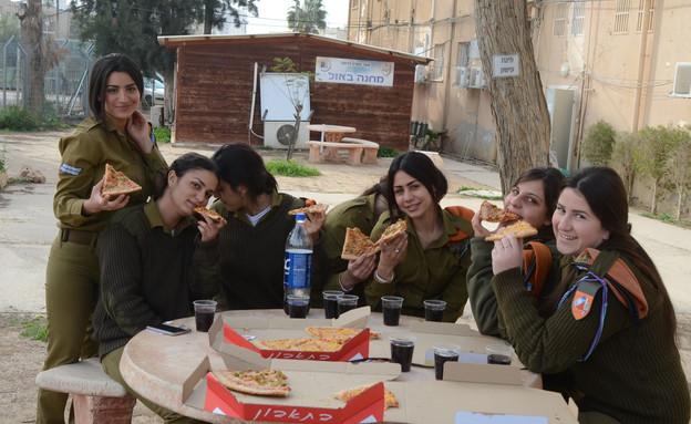 """חיילות פיקוד העורף אוכלות פיצה (צילום: ספיר ברונזברג, עיתון """"במחנה"""")"""