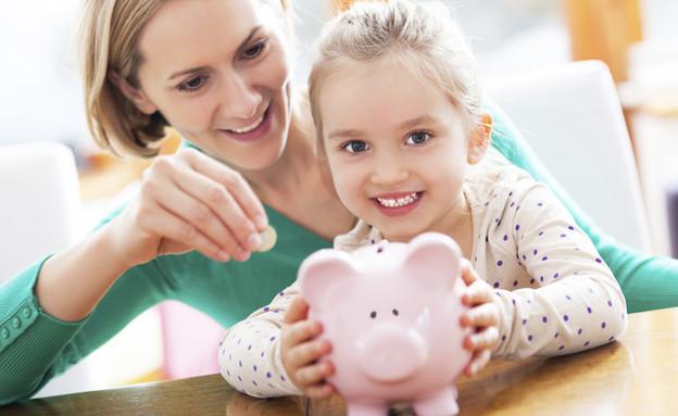 אמא וילדה מכניסות מטבעות לפיל חיסכון (צילום: אימג'בנק / Thinkstock)