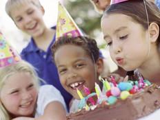 ילדה מכבה נרות על עוגת יום הולדת