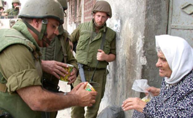 חייל נותן אוכל לאישה פלסטינית