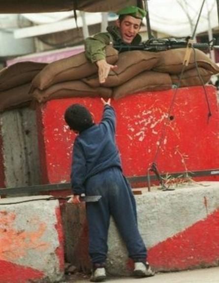 חייל מושיט יד לילד פלסטיני