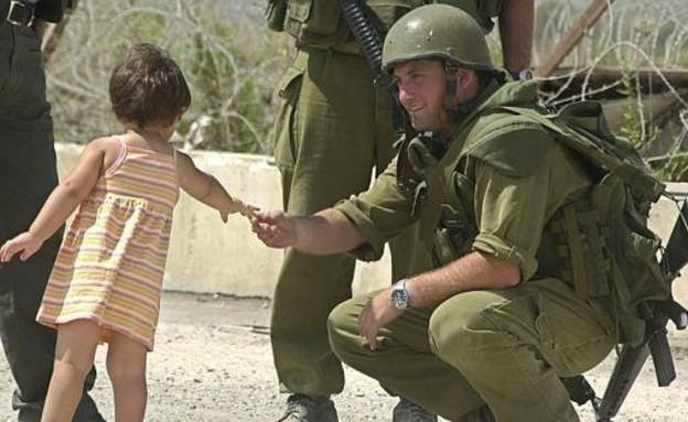 חייל נותן לילדה פלסטינית סוכריה