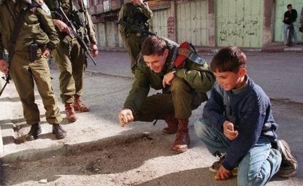 חייל משחק עם ילד פלסטיני