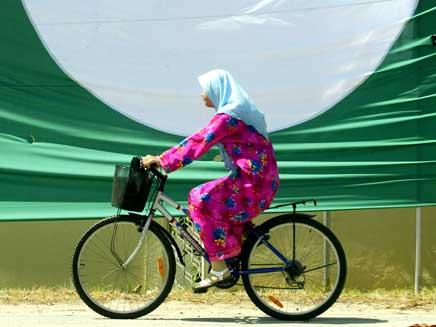 אישה מוסלמית רוכבת על אופניים