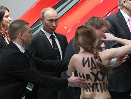 פוטין ומפגינה חשופת חזה (צילום: Sasha Mordovets, GettyImages IL)