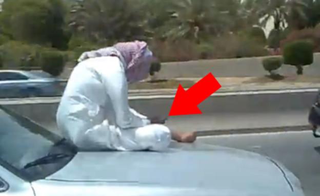 סעודי מסמס על מכסה המנוע של רכב
