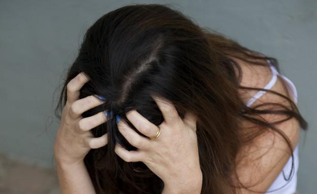 נערה בדיכאון מחזיקה את הראש (צילום: רועי ברקוביץ')