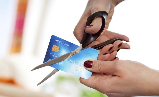 אדם גוזר במספריים כרטיס אשראי (צילום: אימג'בנק / Thinkstock)