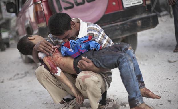ילד מחזיק ילד הרוג בסוריה (צילום: AP Photos/ Manu Brabo)