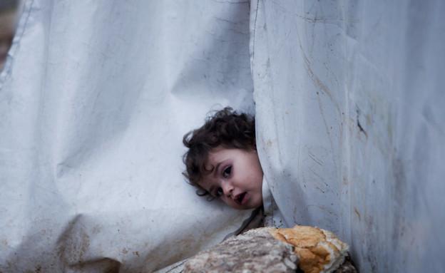 ילדה מציצה בין הריסות (צילום: AP Photos/ Manu Barbo)