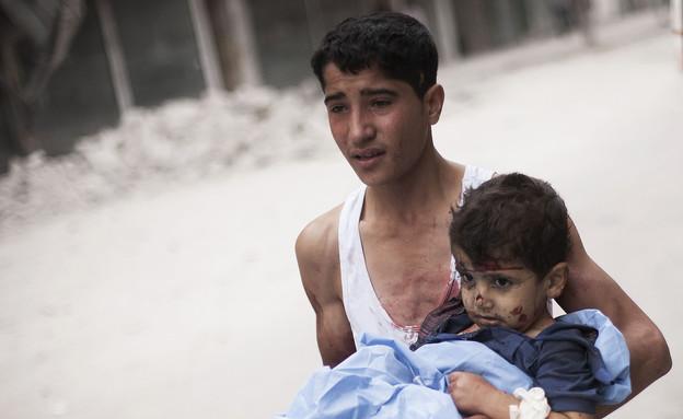 נער מפנה ילד פצוע בסוריה (צילום: AP Photos/ Manu Brabo)