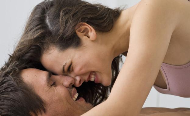 זוג במיטה מחייכים (צילום: Thinkstock)