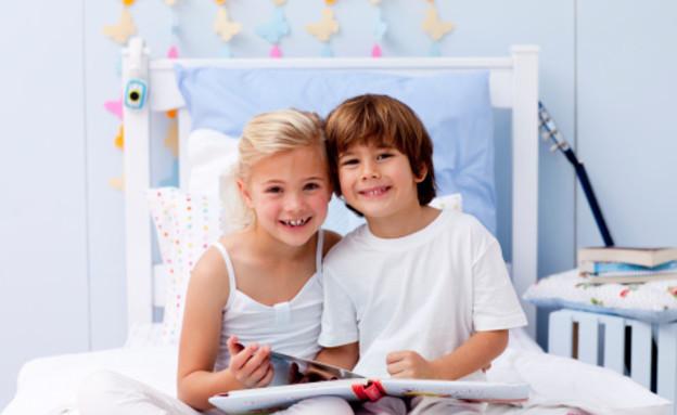 שני  ילדים קוראים ביחד ספר על מיטה (צילום: אימג'בנק / Thinkstock)