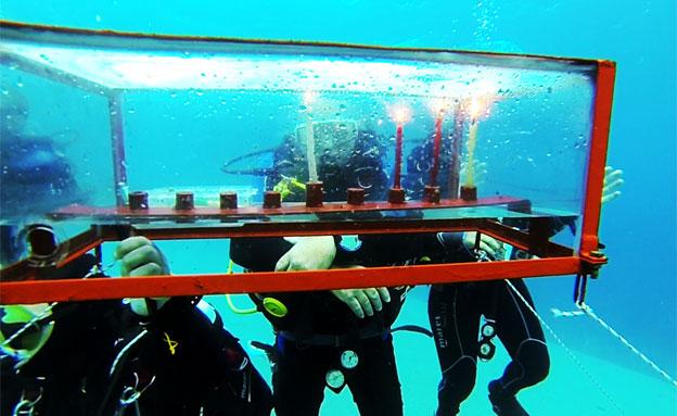 הדלקת הנרות מתחת למים (צילום: אמיר וייצמן, אקווה זום)