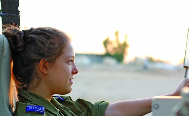 """כתבת במחנה על רכב קרבי (צילום: ספיר ברונזברג, עיתון """"במחנה"""")"""