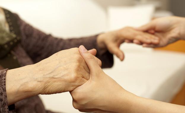 צעירה מחזיקה את ידיה של קשישה (צילום: gece33, GettyImages IL)