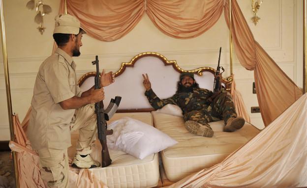 מורדים לובים שוכבים על אחת ממיטותיו של קדאפי (צילום: ap)