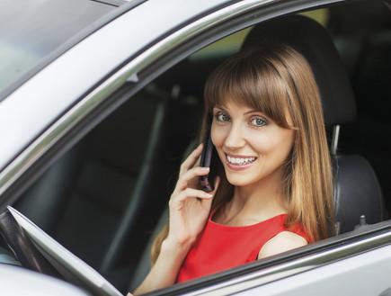 אישה מדברת בטלפון ומחזיקה אייפד ברכב