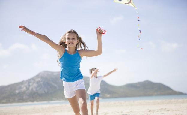 ילדים מעיפים עפיפון בים (צילום: אימג'בנק / Thinkstock)