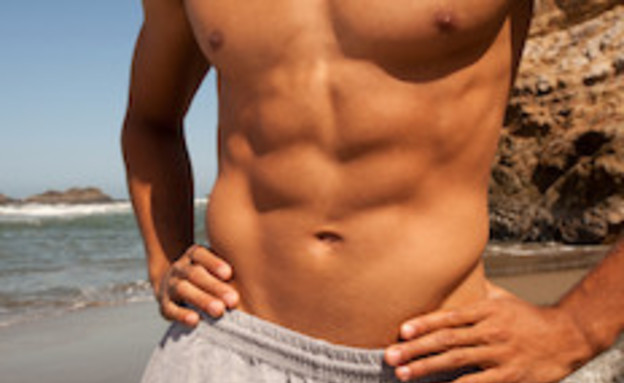 גבר שרירי בחוף (צילום: istockphoto)