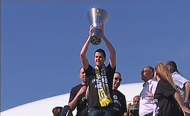 """גיא פניני מניף את הגביע בנתב""""ג (צילום: חדשות 2)"""