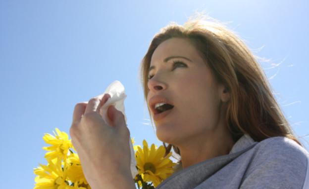 בחורה מתעטשת על רקע פריחה (צילום: אימג'בנק / Thinkstock)