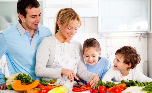 משפחה חותכת ירקות (צילום: kristian sekulic, Istock)