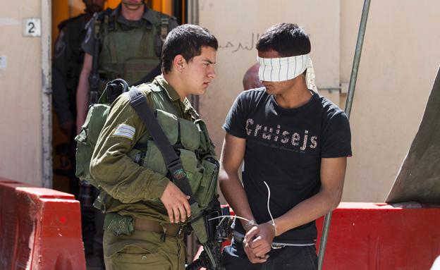 חייל ישראלי ועצור פלסטינאי (צילום: רויטרס)