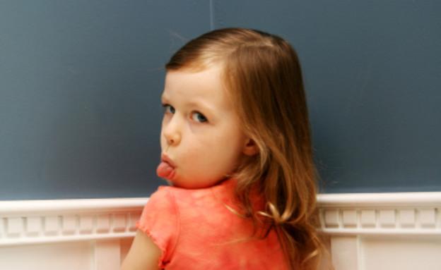 ילדה בפינה מוציאה לשון (צילום: Brad Killer, Istock)