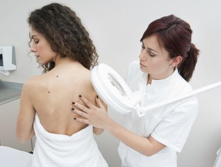 רופאה בודקת גב של אישה