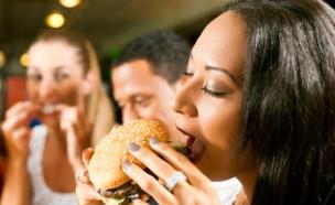 אישה אוכלת המבורגר במסעדה (צילום: אימג'בנק / Thinkstock)