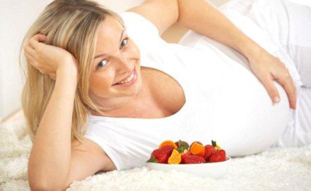 אישה בהריון שוכבת על הצד קערת פירות לצידה (צילום: אימג'בנק / Thinkstock)