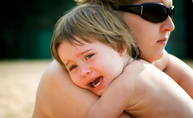 ילד בוכה ומחבק את אמו (צילום: AlexMotrenko, Istock)
