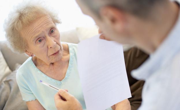 איש מחזיק נייר ועט מול אישה מבוגרת בתכלת (צילום: jupiter images)