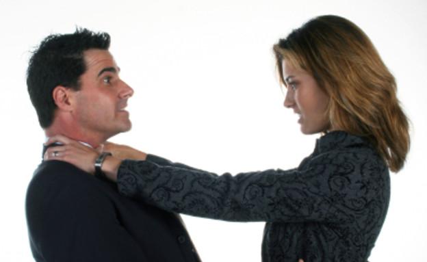 גבר ואישה בשחור רבים והיא חונקת אותו (צילום: אור גץ, istockphoto)