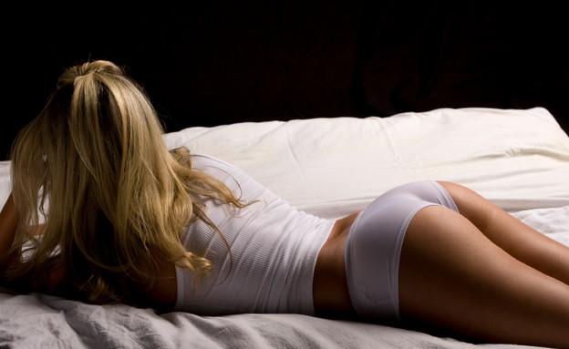 שוכבת על המיטה בתחתונים (צילום: MrPants, Istock)