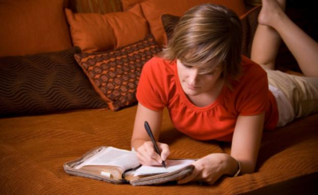 בחורה כותבת מכתב על ספה (צילום: Loretta Hostettler, Istock)