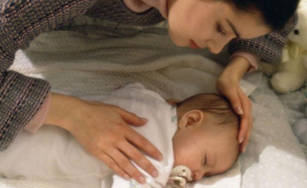 אמא מלטפת את התינוקת שלה שישנה בלול (צילום: jupiter images)