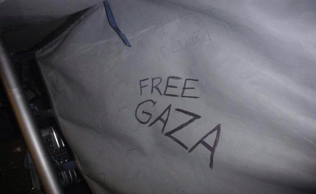 """כיתוב """"FREE GAZA"""" על הרשת בתא מטען במטוס"""