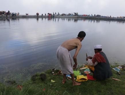מסע טיהור - מאמינים בעת תפילה וטבילה באגם המקודש בדני קונד (צילום: יורם פורת)