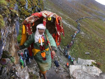 מסע טיהור - עולה רגל הולך יחף ונושא מטריה מקודשת כשמאחוריו טור  (צילום: יורם פורת)
