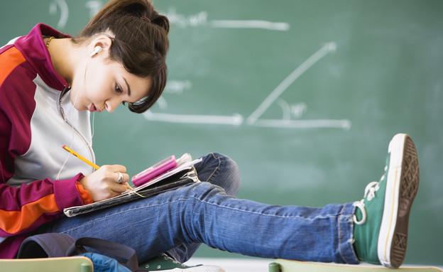 סטודנטית כותבת במחברת (אילוסטרציה: Fuse, Thinkstock)