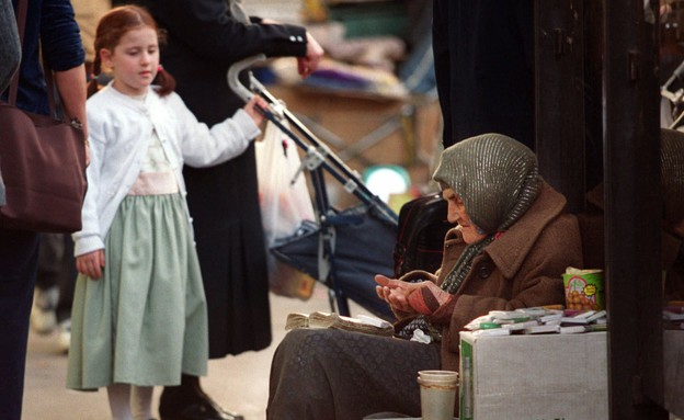 ילדה מסתכלת על קבצנית בירושלים (צילום: ap)