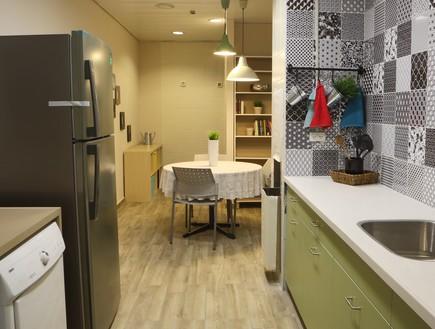 דירת עצמאות סטודיו פנימה 06, מכונת הכביסה מוקמה במטבח ומעליה משטח