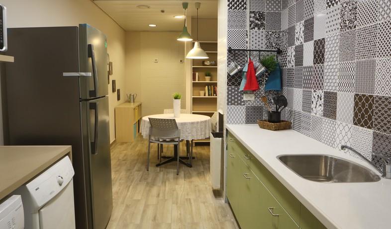 דירת עצמאות סטודיו פנימה 06, מכונת הכביסה מוקמה במטבח ומעליה משטח  (צילום: נועם מושקוביץ)