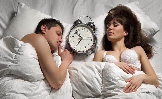 זוג במיטה עם שעון (צילום: Thinkstock)