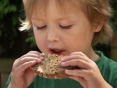 ילד לבוש ירוק אוכל כריך ומביט למטה (צילום: Maartje van Caspel, Istock)