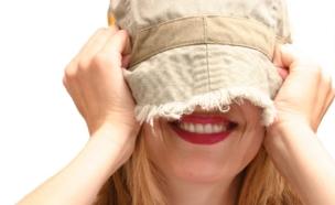 אישה נבוכה - כובע על הפנים (צילום: Sharon Dominick, Istock)