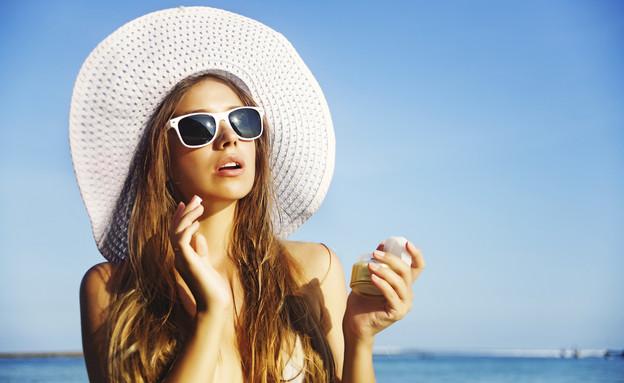אישה במשקפי שמש מורחת קרם שיזוף (אילוסטרציה: LiudmylaSupynska, Thinkstock)